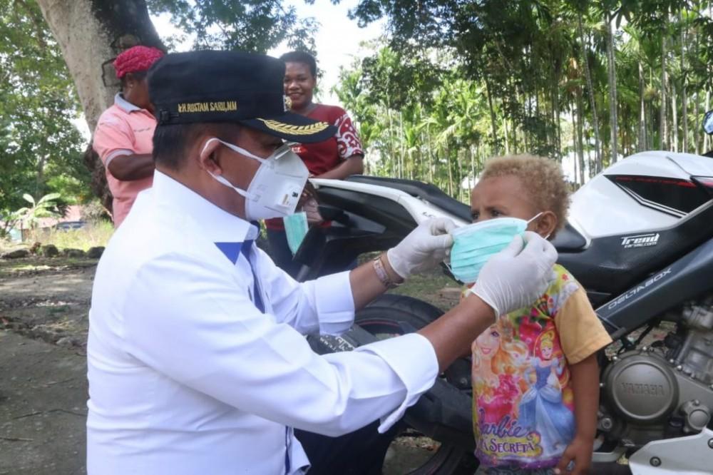 Wakil Walikota Saat Memasang Masker Kepada Salah Satu Anak Kawasan Perbatasan RI-PNG