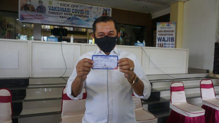 Wakil Walikota menunjukkan kartu sebagai bukti telah menerima vaksin covid-19