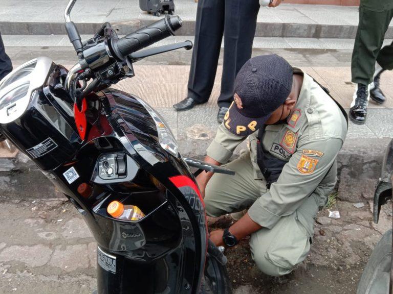 Petugas Sat Pol PP kota Jayapura menggembok motor yang diparkir tidak pada tempatnya